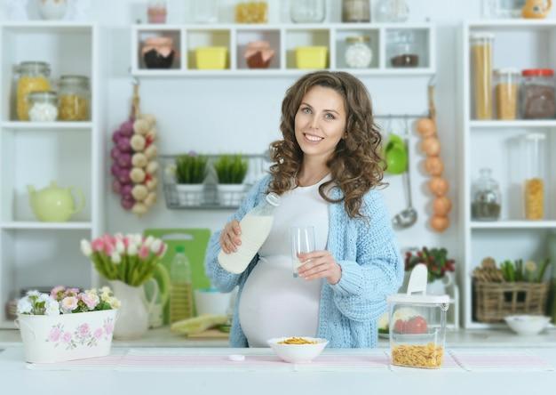 キッチンでミルクと美しい妊婦