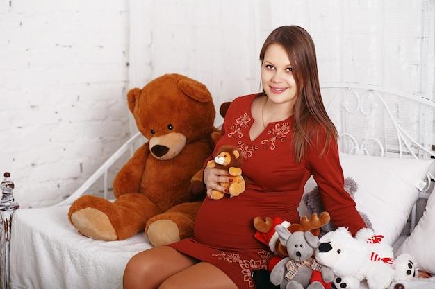 부드러운 장난감으로 아름 다운 임신 한 여자