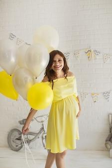 Beautiful pregnant woman in a yellow dress in the studio.