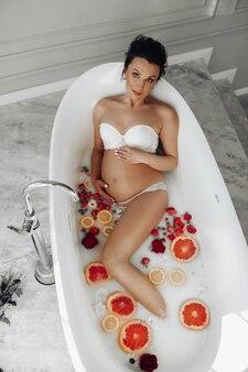 果物、バラ、ミルクでお風呂に入っている腹に触れる美しい妊娠中の若い女性。上面図。健康と妊娠。高品質の写真