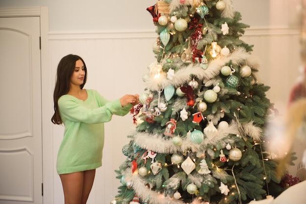 美しい妊娠中の若い女性がクリスマスツリーを飾る