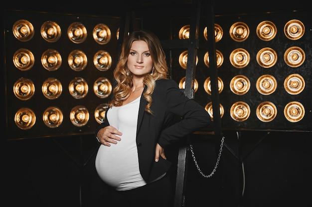 Красивая беременная молодая женщина со светлыми волосами и с нежным макияжем в черной куртке и белой футболке позирует со старинными студийными лампочками на заднем плане