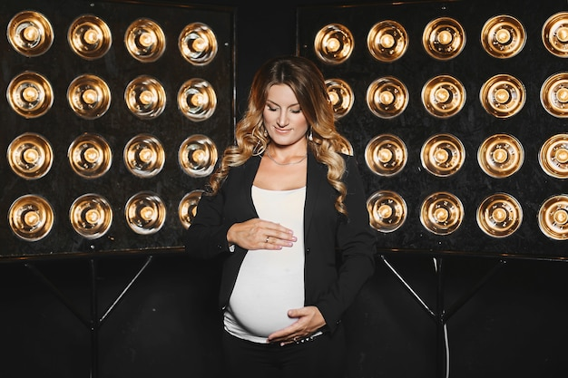 Красивая беременная молодая женщина со светлыми волосами в черной куртке и в белой блузке позирует со старинными студийными лампочками на заднем плане