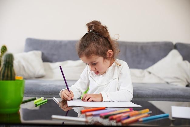 드로잉에 초점을 맞춘 아름 다운 유치원 소녀. 가정에서 유치원 교육의 개념입니다.