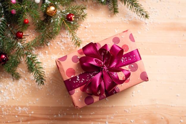 木製のテーブルに大きなピンクの弓で美しいプレゼント