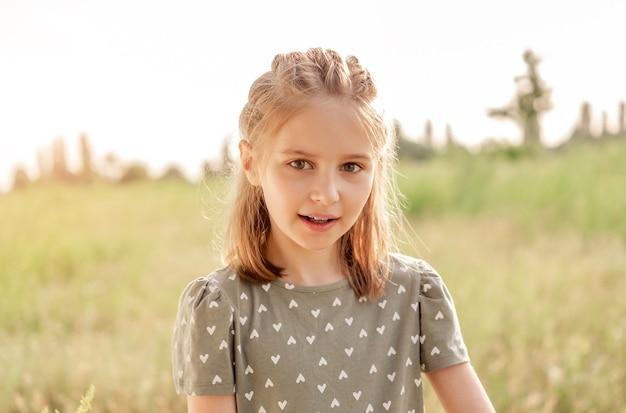 아름 다운 햇살 배경으로 자연에 카메라를 찾고 아름 다운 초반 소녀. 여름 시간에 들판에 헤어스타일을 한 귀여운 여자 아이의 초상화