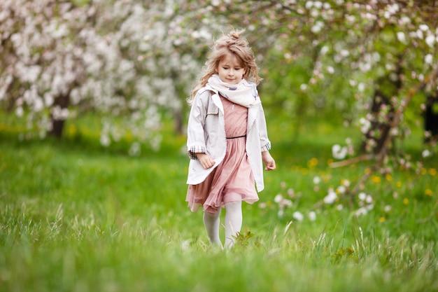 긴 금발 머리를 가진 아름다운 초반 소녀는 봄 사과 개화를 즐길 수 있습니다. 정원 나무 꽃에 작은 유치원 소녀 runing. 봄. 공간 복사