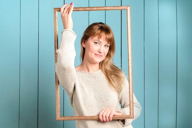 ゆるい髪のニットプルオーバーの美しいきれいな金髪の若い女性は、ヴィンテージの木製の額縁と笑顔を保持します