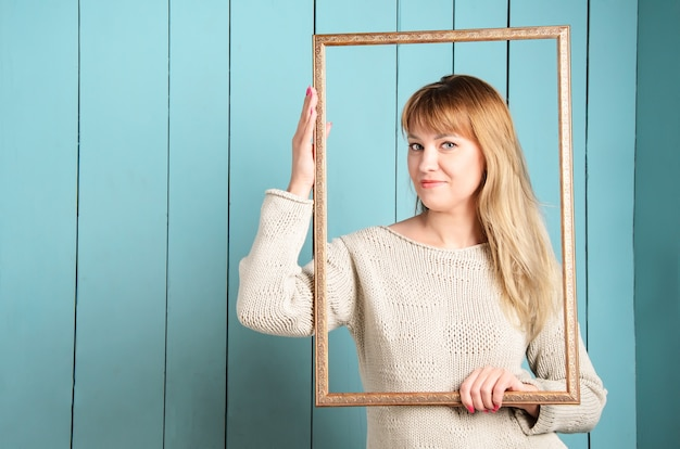 Beautiful pretty blonde young woman in knitted pullover with loose hair holds vintage wooden picture frame and smiles.