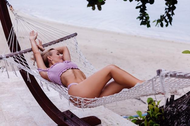 紫色のビキニで美しいかなり白人のブロンドフィット日焼けした女性はハンモックにあります