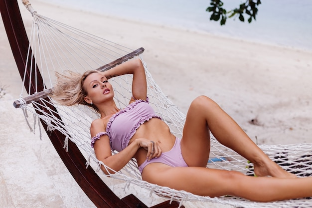 紫色のビキニの嘘で美しいかなり白人のブロンドフィット日焼けした女性