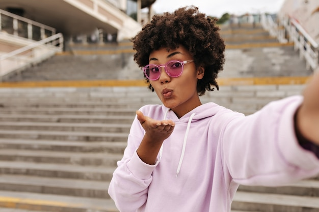 Beautiful pretty curly brunette woman in stylish pink hoodie and colorful sunglasses blows kiss and takes selfie near stairs outside