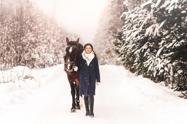 美しいかわいい女の子は冬に森の中で馬と一緒に行きます
