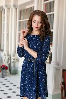 고급 도서관 내부에서 포즈를 취하는 파란색 칼집 칵테일 드레스를 입은 아름다운 소녀. 젊은 여성 모델 패션 초상화