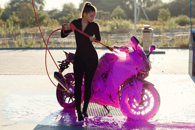 タイトフィットの魅惑的なスーツを着た美しい可愛い女の子が、セルフサービスの洗車サービスでバイクを洗っています。