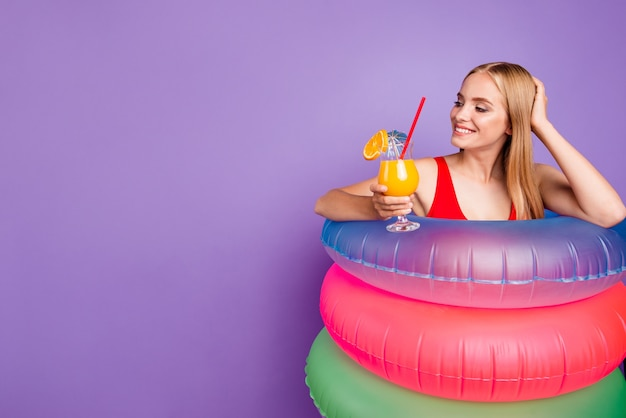 Beautiful pretty lady with colourfull floats around waist holding cocktail
