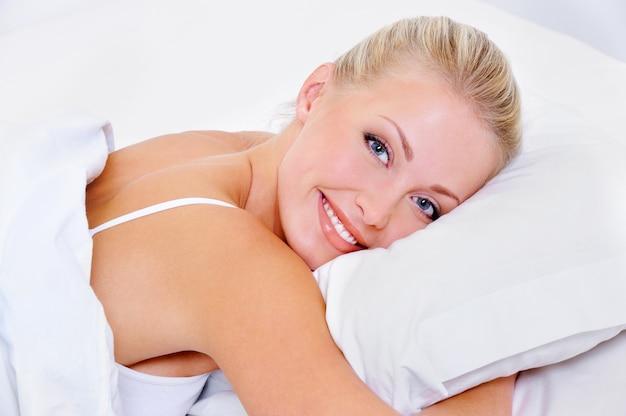 寝た後の魅力的な笑顔で美しいきれいな素敵な女性