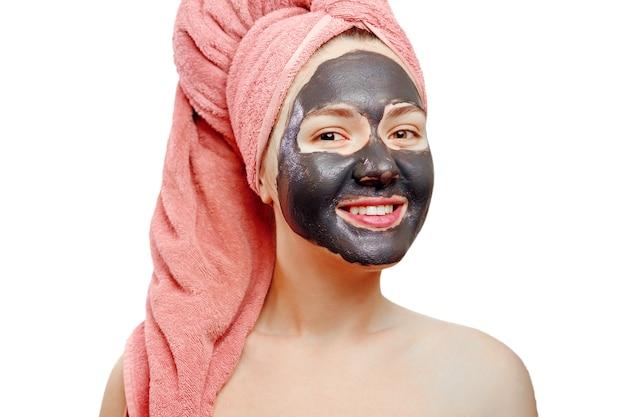 白い背景に黒いフェイスマスク、クローズアップの肖像画、孤立した、彼女の頭にピンクのタオルを持つ女の子、女の子が笑っている、女の子の顔に黒いマスクを持つ美しいかなりセクシーな女の子、楽しんでいます
