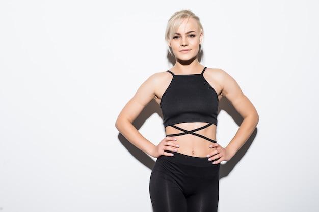 Bello modello femminile abbastanza snello in vestiti di montaggio neri che posano sopra bianco