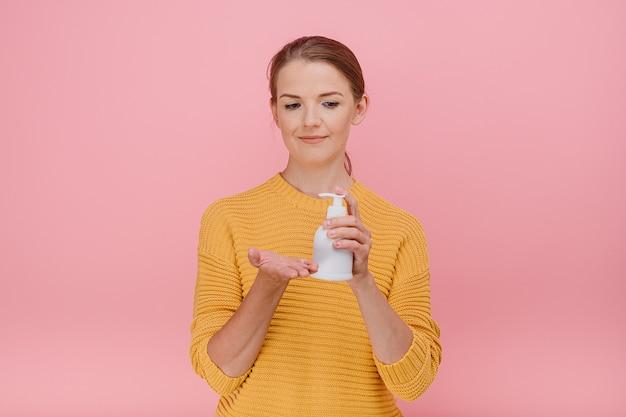 부담없이 옷을 입고 아름다운 예쁜 여자는 살균 소독제 또는 액체 비누를 사용합니다
