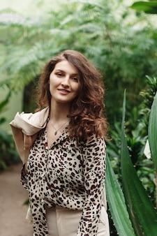 Красивая милая женщина в блузке леопарда на зеленых джунглях