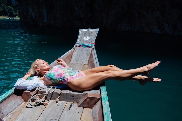보트 가장자리에 수영복에 아름 다운 예쁜 여자