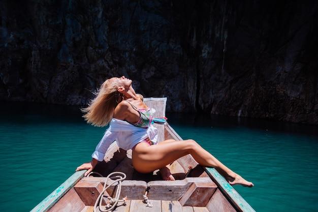 Beautiful pretty woman in swimsuit on edge on boat