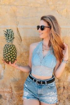 巻き毛を持つ美しいきれいな女性はビーチでパイナップルを保持しています。