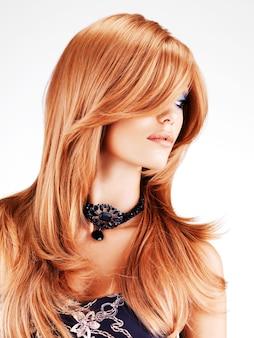 Красивая красивая женщина с длинными рыжими волосами, изолированными на белой стене