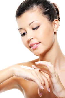 Bella ragazza graziosa che si prende cura della sua crema cosmetica per il trattamento delle mani