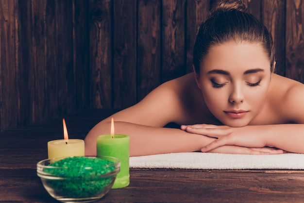 Красивая довольно молодая женщина, лежа в спа-салоне с закрытыми глазами и расслабленной