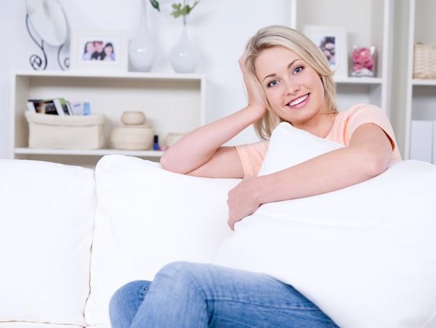 Красивая довольно молодая женщина отдыхает на диване в комфортабельной комнате