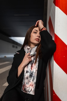Beautiful pretty young woman with brown hair in stylish black coat in vintage elegant silk shawl is resting near a red-white pillar in a city parking lot. attractive european girl fashion model.