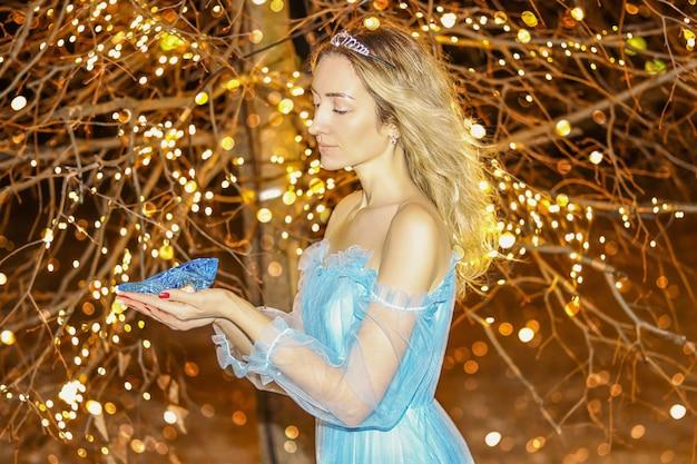 彼女の手に青いクリスタルの靴と明るい黄色の木の背景に青いロングドレスの美しい王女。アート加工。
