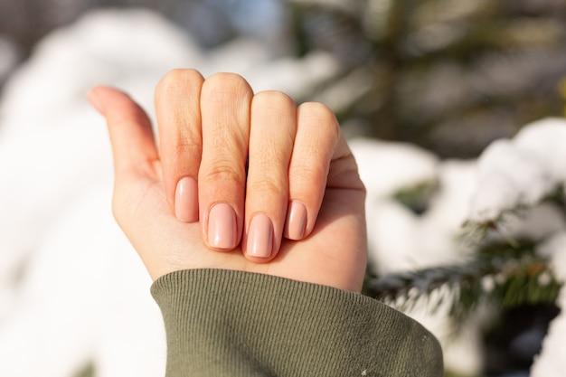 Красивый профессиональный нюдовый бежевый маникюр на женской руке на фоне заснеженного дерева в солнечный день при естественном освещении