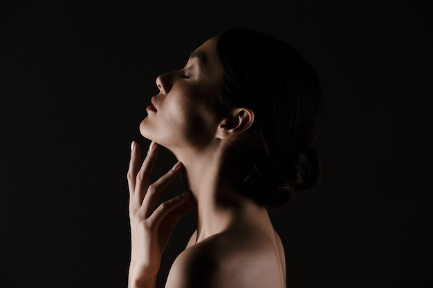 Beautiful in profile of half-naked gentle woman posing on camera with closed eyes isolated, over black