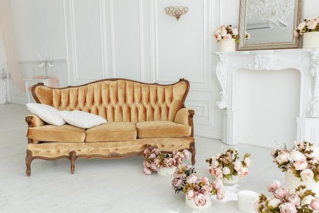 Красивая гостиная в провансе с винтажным коричневым диваном возле камина с цветами и свечами