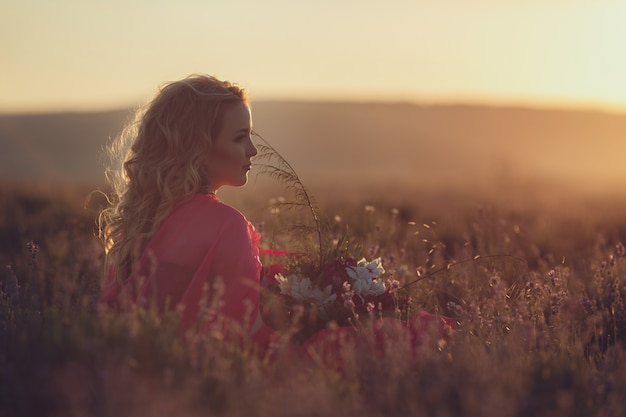 Beautiful provence pregnant woman relaxing in lavender field watching on sunset holding basket with lavanda flowers. series. alluring girl with purple lavender. blond lady in blossom field
