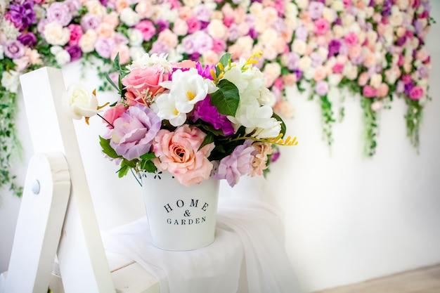 明るい花の壁、造花のバケツと美しいプロヴァンススタイルのインテリア