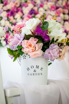 Beautiful provence-style interior with a bright floral wall, bucket with artificial flowers