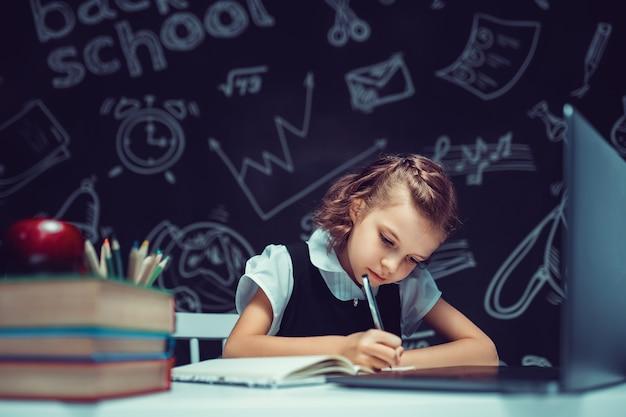Красивый ученик сидит за столом и учится онлайн с ноутбуком на черном фоне