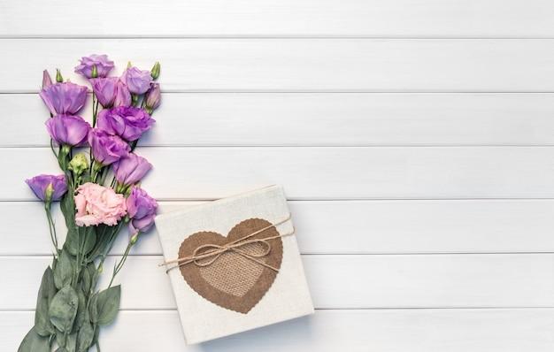 Красивые фиолетовые цветы эустомы и подарочная коробка ручной работы на белом деревянном фоне. копировать пространство, вид сверху,