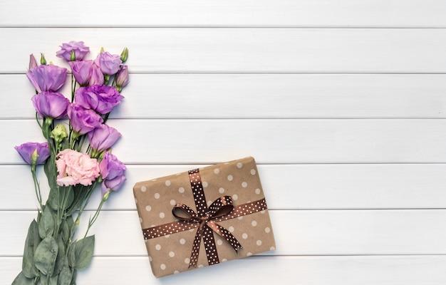 美しい紫色のトルコギキョウの花と白い木製のテーブル、上面図の手作りギフトボックス