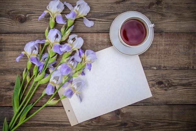 Красивые фиолетовые цветы ирисы, лист бумаги и чашка чая на деревянном деревенском фоне летом, вид сверху, с копией пространства