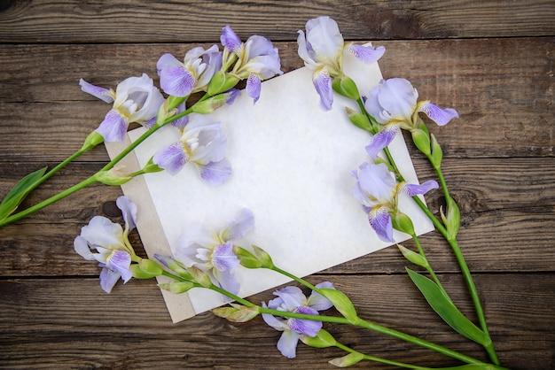 Красивые фиолетовые цветы ирисы и лист бумаги на деревянном деревенском фоне летом, вид сверху, с копией пространства