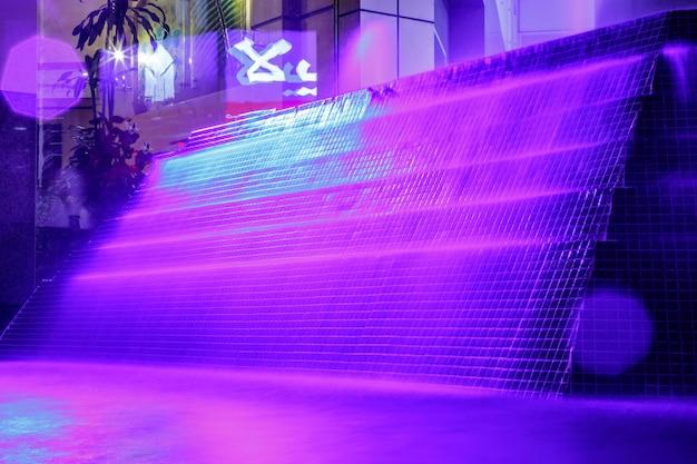 Красивый фонтан с фиолетовой подсветкой ночью в дубае