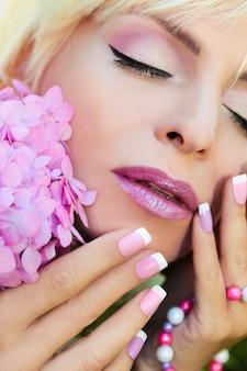 美しい紫色のメイクとフレンチマニキュア