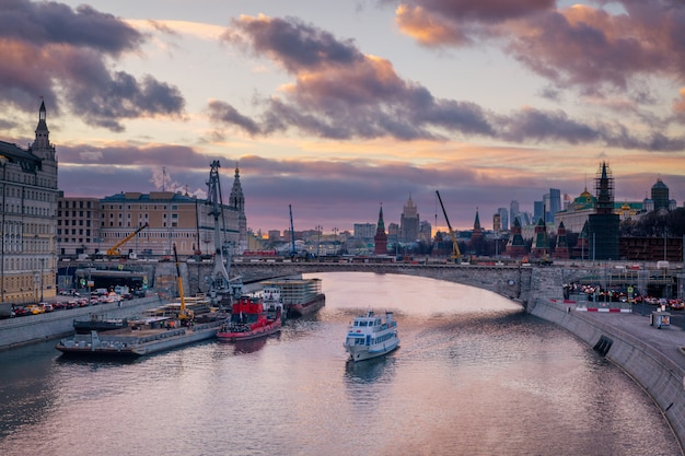 Beautiful purple sunset over moskva river and a touristic boat cruising