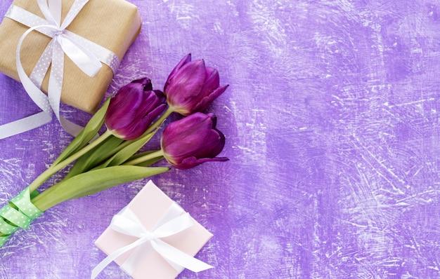 Красивый фиолетовый букет тюльпанов и подарочная коробка на фиолетовом фоне. весенние цветы тюльпаны фон.