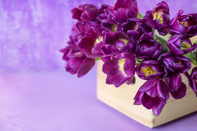 Красивые фиолетовые тюльпаны в деревянной корзине на фиолетовом столе.
